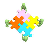 Four puppets, holding in hands a puzzle Royalty Free Stock Photography