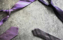 Four purple violet patterned ties on grey grunge scratched table background royalty free stock photos