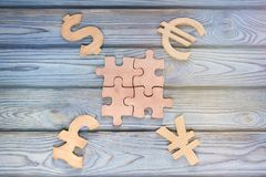 Four puzzle details. Four money currencies on a wooden background. business finance Stock Photography