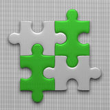 Four puzzle pieces. Connected white puzzle pieces and green ones lying on gray background Royalty Free Stock Photos