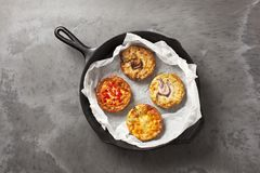 Four quiches in a frying pan. Four freshly baked quiche pies in a cast iron pan on a dark slate effect surface stock image