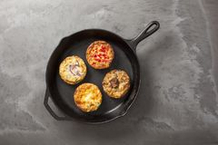 Four quiches in a pan. Four freshly baked quiche pies in a cast iron pan on a dark slate effect surface royalty free stock image
