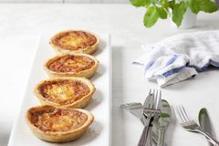 Four quiches on a white plate. Landscape image of four individual mini quiche pies on a white rectangular plate with a tea towel and cutlery royalty free stock image