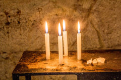 Four quiet candles, flickering in a secluded room Stock Image