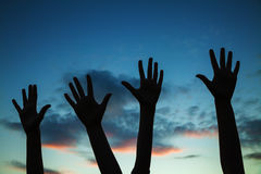 Four raised hands. Against twilight sky Royalty Free Stock Image