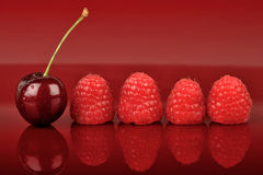 Four Raspberries and One Cherry. One cherry and four raspberries on the red background stock photo