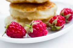 Four raspberries on plate, pancakes background royalty free stock images