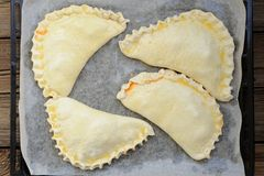 Four raw calzone pizzas on papered frying pan Royalty Free Stock Photography