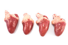 Four raw chicken hearts. Isolated on white Stock Photography