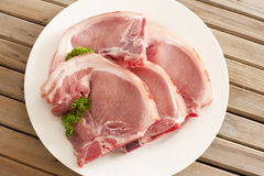 Four raw pork cutlets on a plate Stock Images