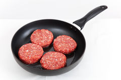 Four raw red meatballs in a black pan Stock Photography