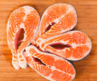Four raw salmon steaks. Four fresh raw salmon steaks are laying  on the cutting board Royalty Free Stock Images