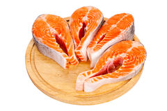Four raw salmon steaks. Four fresh raw salmon steaks are laying  on the cutting board Stock Photos