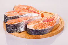 Four raw salmon steaks. Four fresh raw salmon steaks are laying  on the cutting board Stock Photography
