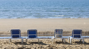 Four reclining sun loungers over looking the sea. Three blue, one stripped sun loungers over looking a blue sea stock photos