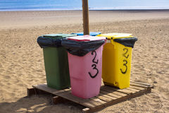 Four recycle bins for different waste. Paper, glass, food, plastic. Beach, sand. Four recycle bins for different waste colored. Paper, glass, food, plastic royalty free stock images