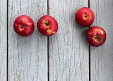 Four red apples on gray wood Royalty Free Stock Photos