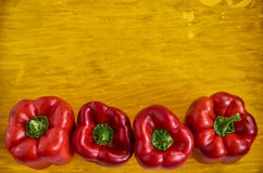 Four red bell peppers close up on wooden yellow background with copy space. Bell peppers on wooden yellow texture close up Royalty Free Stock Photo
