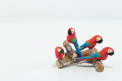Four red, blue and green Macaws perched on a wood trunk isolated Stock Photo
