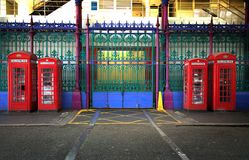 Four red english phone booths. Four red booths in two different sizes with green, purple  and blue iron fence in background in Smithfield market in London UK Stock Image