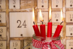 Four red burning advent candles with calendar. Stock Photos