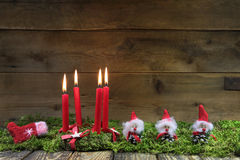Four red burning christmas candles on wooden background with gre Stock Photos