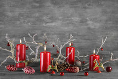 Four red burning wax advent candles on wooden natural grey backg Royalty Free Stock Image