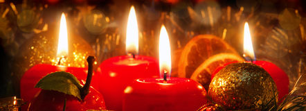 Four red candles with christmas ball in atmospheric light. Stock Photo