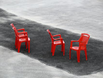 Four red chairs on dark asphalt stripe Royalty Free Stock Image