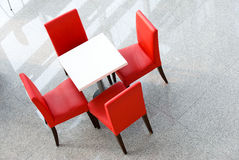 Four red chairs at a table Stock Photography