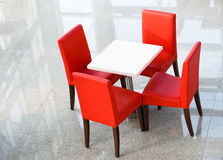 Four red chairs at a table Stock Images