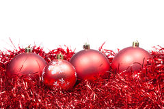 Four red Christmas balls and tinsel isolated stock photos
