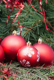 Four red Christmas balls and Xmas tree background Royalty Free Stock Photography