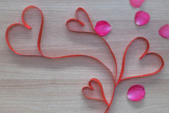 Four red heart shape ribbon with pink rose petals on wooden surface with empty space for text Royalty Free Stock Photo
