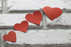 Four red heart Valentine`s Day, white brick wall background Stock Images