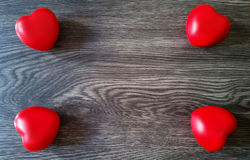 Four red hearts background. Four red hearts on a dark wooden background Royalty Free Stock Photos