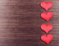 Four red hearts on a dark wooden board Stock Photos