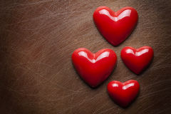 Four red hearts on scratched background Royalty Free Stock Image