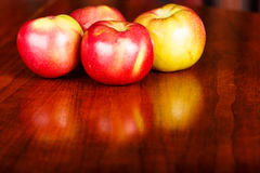 Red Apples on a Shiny Wood Table Stock Image