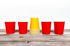 Four red and stack of yellow paper disposable cups for coffee and nonalcoholic drinks on wooden background stock photo