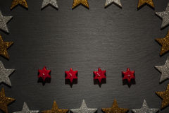 Four red star candles on slate with star frame Royalty Free Stock Photos