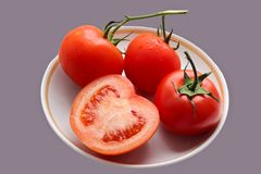 Four red tomatoes on a plate. Stock Photos
