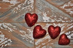 Four red Valentine hearts on a rough wooden board background. stock photos