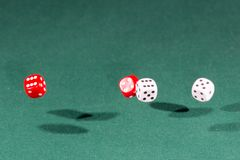 Four red and white dices falling on a green table stock images