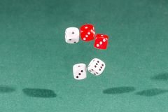 Four red and white dices falling on a green table stock photo