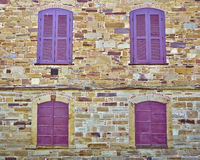 Four red windows on stone wall Stock Photography