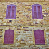 Four red windows on stone wall Royalty Free Stock Images