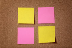 Four reminder sticky notes on cork board Stock Photo