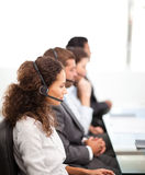 Four representatives on the phones with earpiece Stock Image