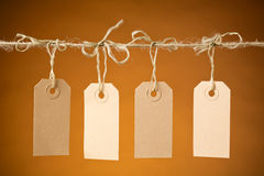 Four Retail Price Labels. Four blank paper price tag labels hanging next to each other on a rope with orange background Stock Photos